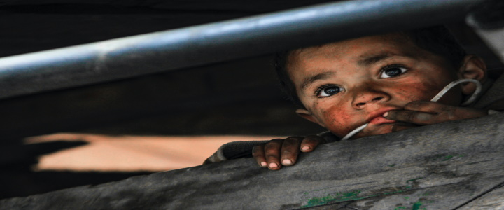 A dirty child with a sad or thoughtful expression looks out from a hiding place.