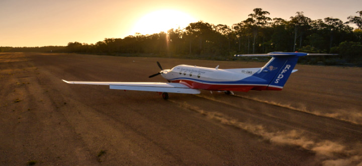 A small aircraft of the RFDS (Royal Flying Doctor Service) landing on a bare earth runway
